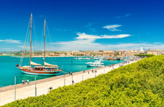 Beautiful view of a promenade in Syracuse with walking people. Cityscape of Ortygia Island with harbor, embankment, park and ships