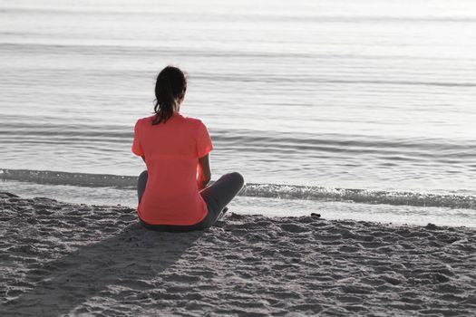 Young woman sitting on the shoreline of the sea at dawn in athletic outfit, looks towards the sea illuminated by the low sun and meditates