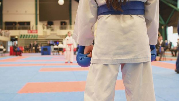 Sports teenagers - kid sportsmen at karate tatami - ready for fight, close up