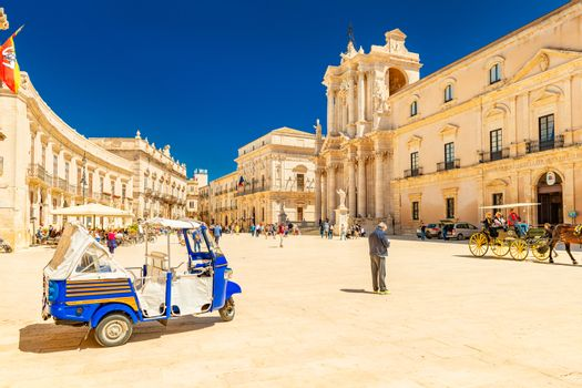 Ortygia - April 2019, Syracuse, Italy: View of The Cathedral of Syracuse and the central square (Piazza Duomo) with walking people