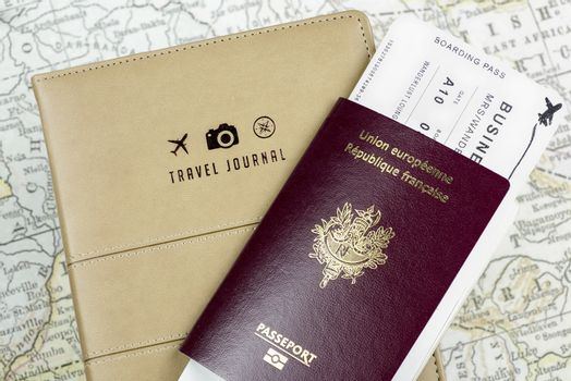 Close-up of a Travel Journal cover with 3 small logos (a plane, a camera and a compass), a passport and a boarding pass and a ancient map at background.
