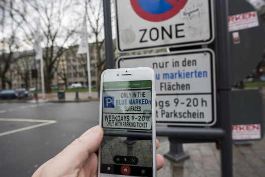 Man using augmented reality apps (here Google Translate) to translate text from german to english instantly with his iPhone