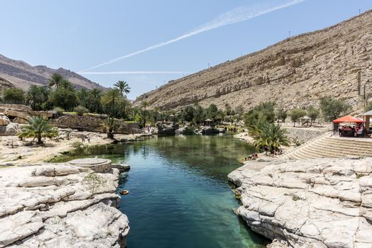 Tourists close to the river (with turquoise water) and pool of Wadi Bani Khalid, Oman