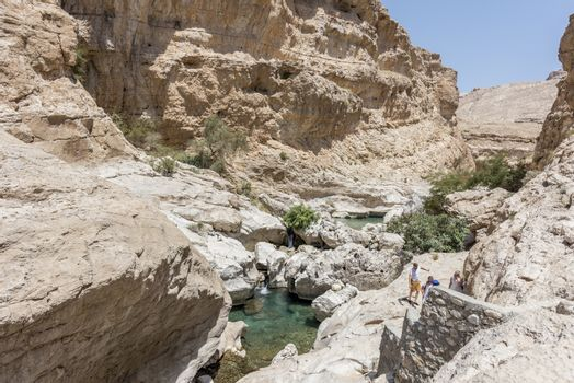 Tourists and guide trekking near the river and pool in the canyon of Wadi Bani Khalid,  in Oman