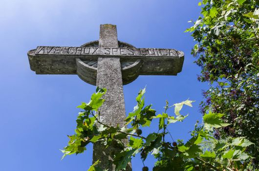 """Old stone christian cross on a bright sunny day. """"Ave crux, spes unica"""" is a Latin pious expression or motto meaning """"Hail to the Cross, our only hope."""""""