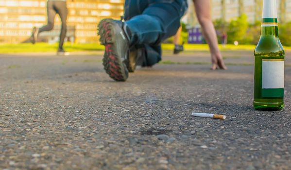 a discarded cigarette lies near a beer bottle on the asphalt path next to a man who is preparing to run a sprint through the city stadium