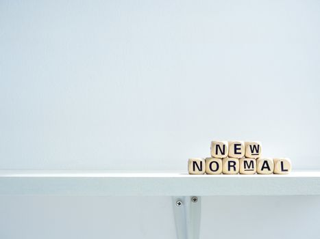 New Normal, words on wooden alphabet cube on shelf on white background with copy space. New normal after covid-19 pandemic concept.