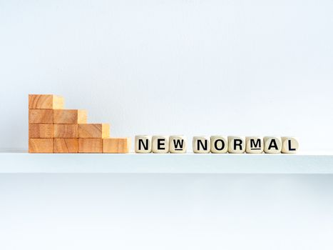 Stairs down to New Normal, words on wooden alphabet cube on shelf on white background with copy space. New normal after covid-19 pandemic concept.