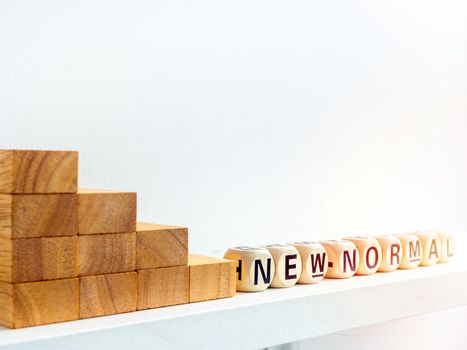 Stairs down to New Normal, words on wooden alphabet cube on white background with sunlight. New normal after covid-19 pandemic concept.