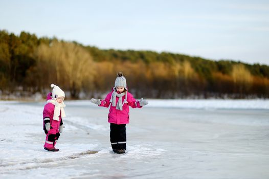 Two little sisters having fun on white and snowy winter day