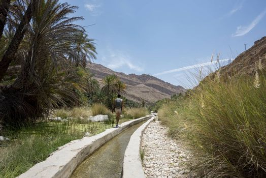 Woman walking near an artificial canal with water in the famous Wadi Bani Khalid in the Sultanate of Oman