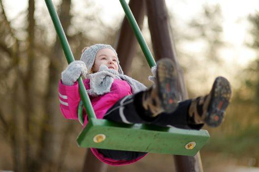Adorable girl having fun on a swing on beautiful winter day