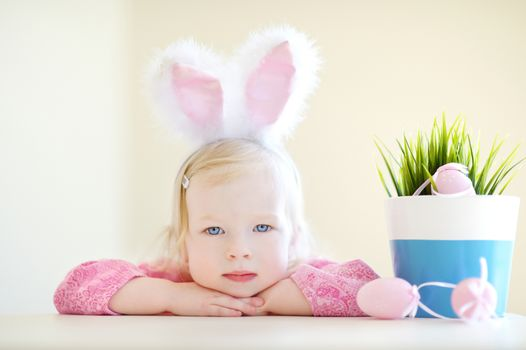 Adorable toddler girl wearing bunny ears playing with colorful Easter eggs