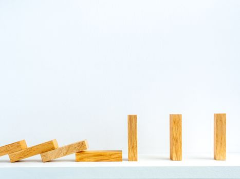 Social Distancing concept. Row of falling and standing wooden dominoes with distance space on shelf on white background with copy space.