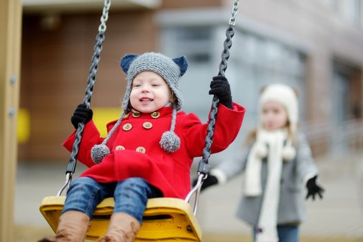 Two little sisters having fun on a swing on early spring