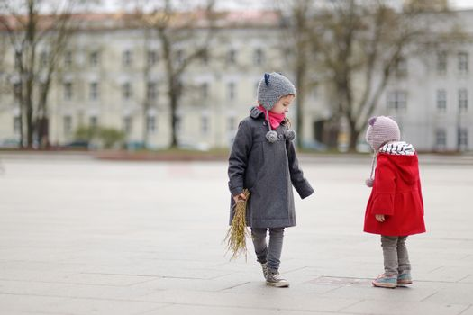 Two adorable little sisters holding willow branches and other plants as part of Easter tradition in Lithuania