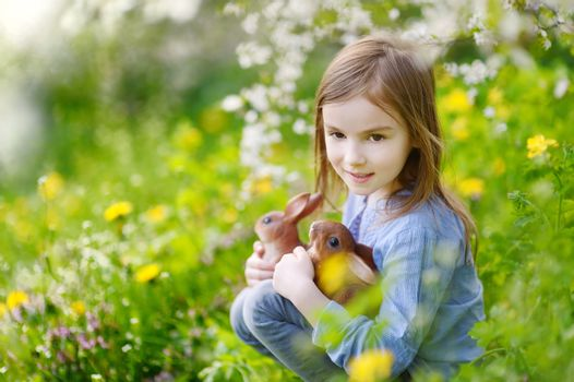 Adorable little girl in blooming cherry garden holding two easter bunnies on beautiful spring day