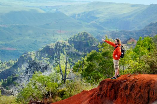 Young man enjoying stunning view into Waimea Canyon, Kauai, Hawaii