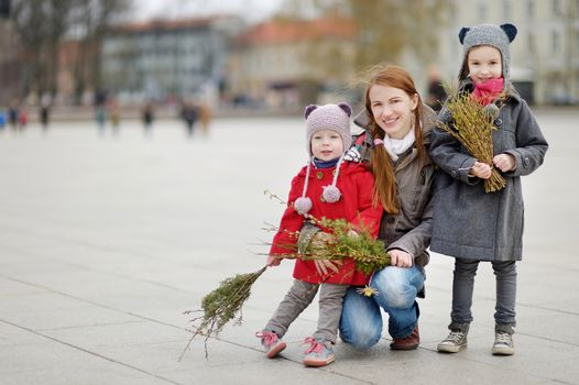 Adorable little girls and their mother holding willow branches and other plants as part of Easter tradition in Lithuania