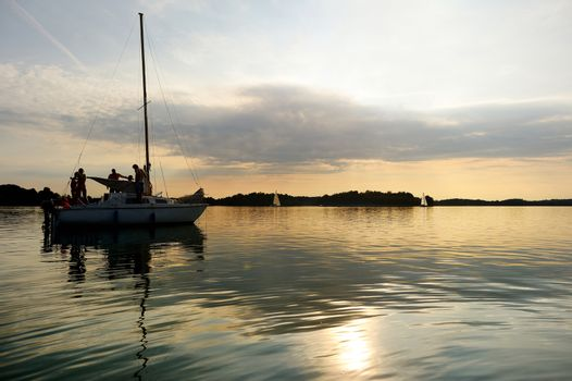 Yacht sailing towards sunset on Trakai lake in Lithuania