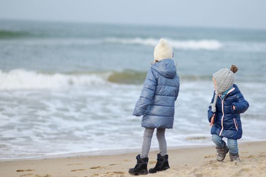 Adorable little sisters playing by the ocean on cold winter day