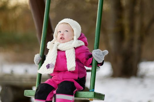 Adorable girl having fun on a swing on beautiful winter day