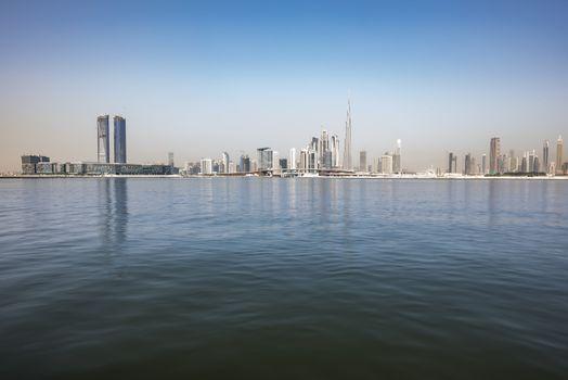 Dubai Skyline with the water canal, Dubai Design district (left) and Burj Khalifa the iconic skyscraper, Ras Al Khor, Dubai, United Arab Emirates