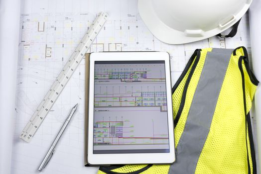 Digital tablet with design drawing, hard copy of drawing, triangular scale ruler and work Personal Protective equipment (safety yellow fluorescent gilet and white helmet)