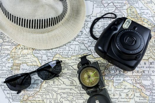 Photography of an ancient Map with a vintage Camera, sunglasses, compass and white hat (Fedora)