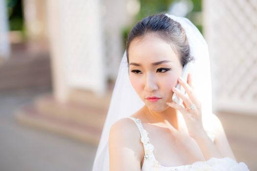 bride talking on cell phone in wedding dress