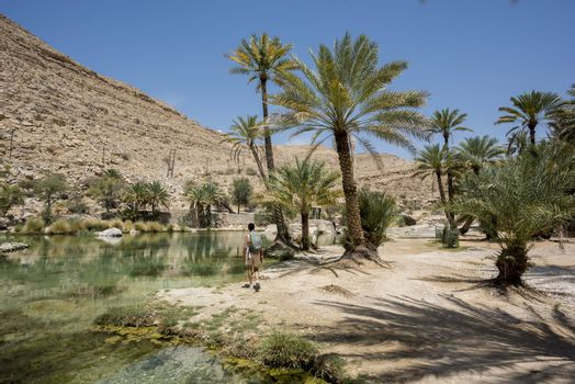 Woman (tourist) walking near the main pool  of the famous Wadi Bani Khalid in the Sultanate of Oman