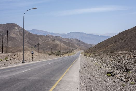 Empty road in Oman wild and arid mountains going thru a wadi. This way is leading to Wadi Bani Khalid