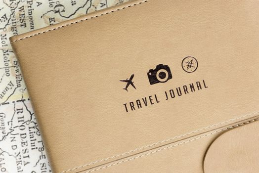 Close-up of a Travel Journal cover with 3 small logos (a plane, a camera and a compass) and a ancient map at background.
