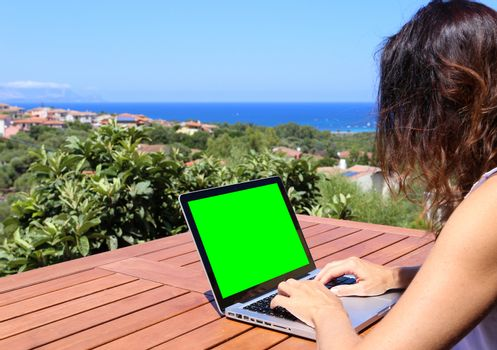 A young woman works on her laptop with the green screen with the blue sea panorama in the background in selective focus
