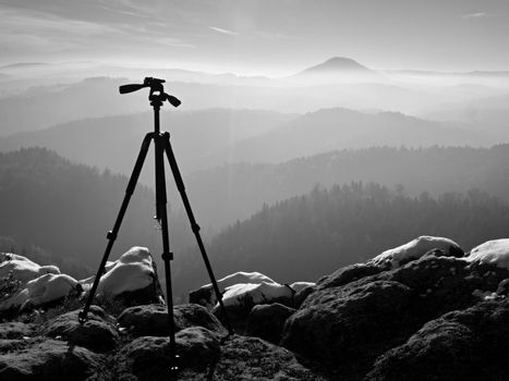 Professional  tripod without camera on snowy peak ready for photography. Snowy sandstone boulders,  first strong sun rays.