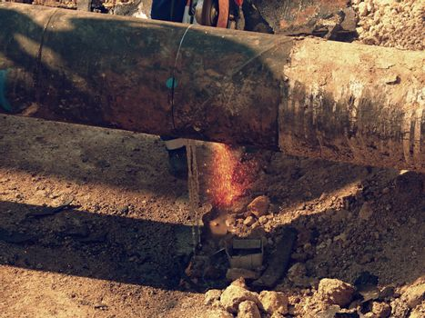 Man works, big pipe cutting with electric spiral machine. Hor sparks flying away from cut place.