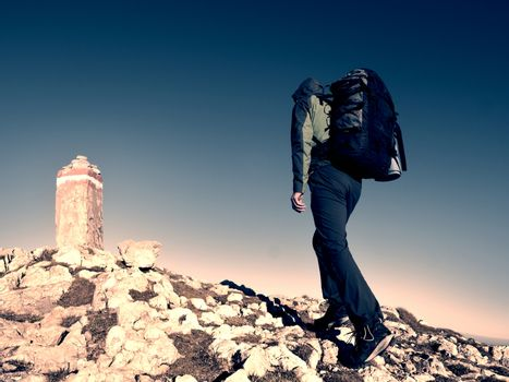 Hiker with backpack climbing on mountain peak. Summit stone at Alps mountain top. Tourist walk with  heavy backpack