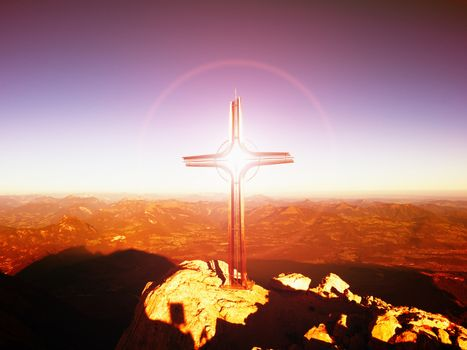 Lens flare light, strong effect.  Cross on peak of Hoher Goell. Iron crucifix at mountain top in Alp at Austria Germany border.  View to Tennen Range and Dachstein range, Berchtesgaden Alps.