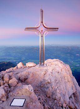 Peak of Hoher Göll. Iron cross at mountain top in Alp at Austria Germany border.  View to Tennen Range and Dachstein range, Berchtesgaden Alps.
