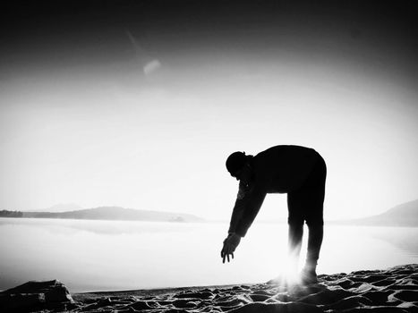 Deep breathing runner silhouette bended  with hands on knees. Side view to sports active man stretching muscles and exercise at sea beach. Sun reflection in smooth water level.