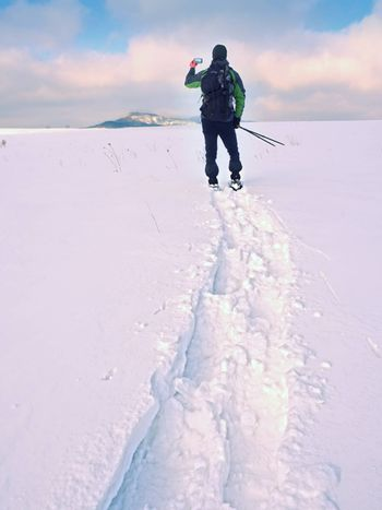 Man with snowshoes and backpack take photos by smartphone. Hiker in snowdrift,  snowshoeing in powder snow. Cloudy winter day, gentle wind brings small snow flakes