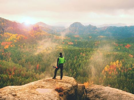 Tall adult  photographer prepare camera for taking picture of fall  mountains. Photograph at daybreak above  colorful  valley. Landscape view of autumn mountain hills and hiker above