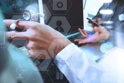 medical doctor hand working with smart phone,digital tablet computer,stethoscope eyeglass,on wooden desk,virtual graphic interface icons screen