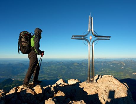 Hiker at big crucifix on mountain peak. Iron cross at Alps mountain top. Tourist with poles and heavy backpack