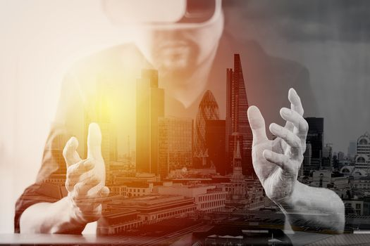 businessman wearing virtual reality goggles in modern office with mobile phone using with VR headset with London city exposure