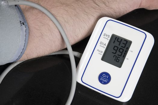 Man measuring his blood pressure at home with an automatic blood pressure monitor. Picture of the machine and arm of the person with results of the test on the screen
