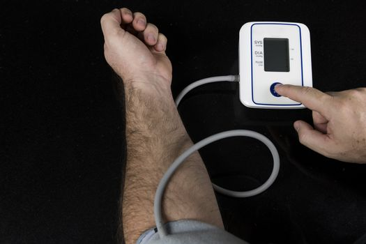 Man measuring his blood pressure at home with an automatic blood pressure monitor. Picture of the machine and arm of the person with a finger pressing the srart button