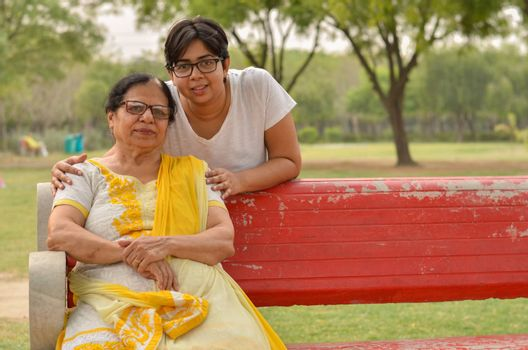 Happy looking young Indian woman with her mother sitting on a red bench in a park in New Delhi, India. Concept Mother's day