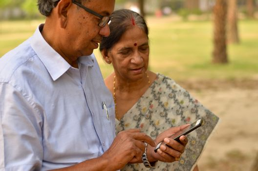 Senior Indian Bengali couple in park looking at their smart phone and smiling in a park in New Delhi, India. Concept love