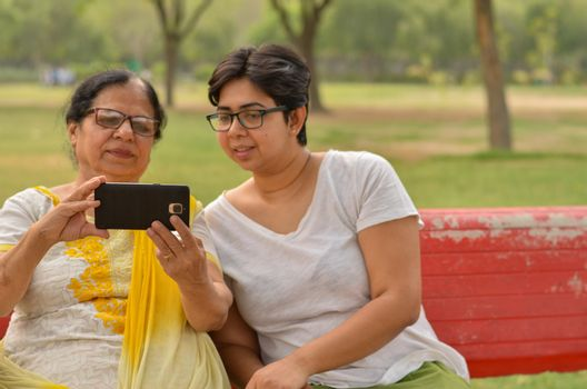 Young Indian girl with her old Indian mother looking at the mobile phone and busy talking selfie on a red bench in a park in New Delhi, India